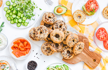 Assorted bagels sorrounded by toppings including fresh cut vegetables salmon and cream cheese