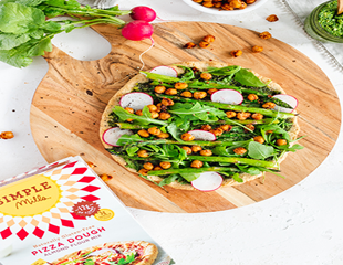 Spring vegetable pizza on round wooden plate on countertop with Simple Mills pizza dough box
