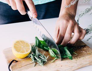 Woman's hand chopping fresh herbs on cutting board with fresh lemon