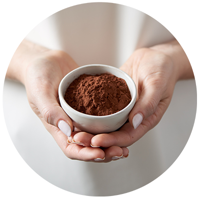 Cocoa ingredient being cradled in a bowl in hands, nothing artificial ever